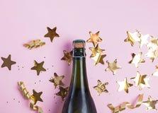 Champagne blänker, och stjärnan formade guld- konfettier på den rosa bakgrunden arkivbild