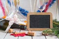Champagne and  blackboard. Bottle of champagne and decorations next to empty blackboard for your text on wooden table. Christmas or New Year`s drink Royalty Free Stock Photo