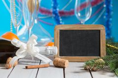 Champagne and  blackboard. Bottle of champagne and decorations next to empty blackboard for your text on wooden table. Christmas or New Year`s drink Stock Photography