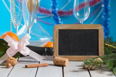 Champagne and  blackboard. Bottle of champagne and decorations next to empty blackboard for your text on wooden table. Christmas or New Year`s drink Royalty Free Stock Photos