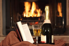 Champagne and a book in front of fireplace Stock Photo