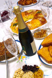 Champagne Bottle. Fluted glass and champagne bottle in a Christmas celebrating table with food Stock Image