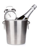 Champagne bottle in bucket and alarm clock Stock Photo