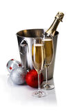 Champagne bottle in bucket with glasses of champagne. And christmas balls  on white background Royalty Free Stock Images