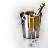 Champagne bottle in bucket with glasses of champagne. In front of bokeh background Royalty Free Stock Photo