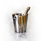 Champagne bottle in bucket with glasses of champagne. In front of bokeh background Royalty Free Stock Photography