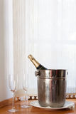 Champagne bottle in bucket and two glasses Stock Photography