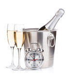 Champagne bottle in bucket, two glasses and alarm clock Stock Photos