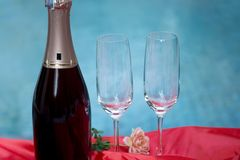 Champagne bottle and champagne glass with red tablecloth royalty free stock photography