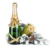 Champagne bottle, christmas gift and snowy firtree Stock Photos