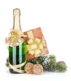 Champagne bottle, christmas gift and snowy firtree Royalty Free Stock Image