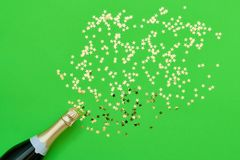 Champagne bottle with confetti stars on green background. Color of the Year 2019. Copy space, top view. Champagne bottle with confetti stars on green background royalty free stock photography