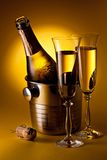 Champagne bottle in cooler and in glasses. Royalty Free Stock Image