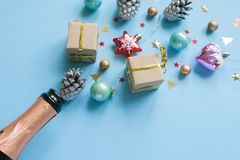 Champagne bottle with different christmas decoration on blue background. New year concept. Champagne bottle with different christmas decoration on blue stock image