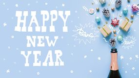 Champagne bottle with different christmas decoration on blue background. New year concept. Lettering happy new year. Champagne bottle with different christmas royalty free stock images