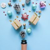 Champagne bottle with different christmas decoration on blue background. New year concept. Champagne bottle with different christmas decoration on blue stock photography