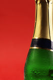 Champagne bottle with drops on red background Stock Photos