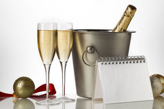 Champagne bottle flutes and ice bucket with christmas baubles Stock Images