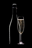 Champagne bottle and full flute. Champagne bottle with full flute glass in shadow on black background Stock Image
