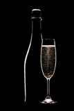 Champagne bottle and full flute. Champagne bottle with full flute glass in shadow on black background Royalty Free Stock Photography