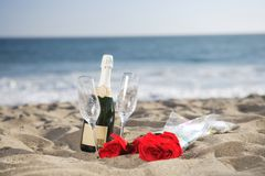 Champagne Bottle, Glasses, Roses at the beach Royalty Free Stock Photos