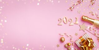 Champagne bottle, golden gift or present box, 2021 number and confetti on pink background top view. Christmas and New Year card.
