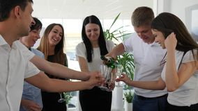 Champagne bottle In hands of businessman at work in office space. Champagne bottle In hands of businessman and employees are holding glasses at work in office stock footage