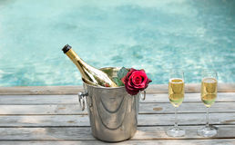 Champagne bottle in ice bucket and champagne glass by swimming p Stock Photo