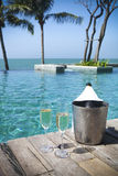 Champagne bottle in ice bucket and champagne glasses. By swimming pool Stock Photos