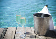 Champagne bottle in ice bucket and champagne glasses. By swimming pool Stock Photo