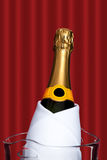 Champagne bottle in ice bucket. With a red curtain in the background Royalty Free Stock Image
