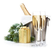 Champagne bottle in ice bucket, two glasses and christmas gift Stock Photo