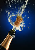 Champagne bottle ready for celebration. Champagne splash. Bottle and cork, celebration time Royalty Free Stock Image