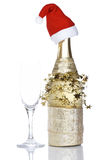 Champagne bottle with red christmas hat. Reflected on white background. Shallow depth of field Stock Images