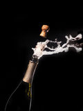 Champagne bottle and spray on black backgroun Royalty Free Stock Images