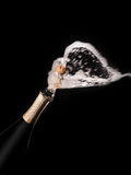 Champagne bottle and spray on black backgroun Royalty Free Stock Image
