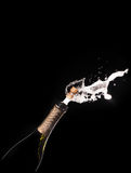 Champagne bottle and spray on black backgroun Royalty Free Stock Photography