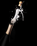 Champagne bottle and spray on black backgroun Stock Photos
