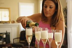 Champagne. Pretty girl pouring champagne in glasses for a celebration toast Royalty Free Stock Photo