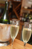 Champagne bucket. Champagne bottle being chilled in a bucket with two filled glasses of champagne in front Royalty Free Stock Images