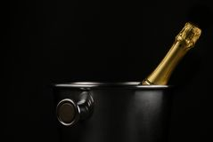 Champagne bucket. Close up of a champagne bottle in a bucket over black background Royalty Free Stock Photo