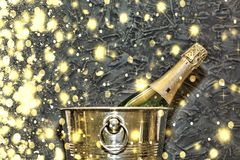 Champagne in a bucket for ice against a stone wall. Golden snowflakes, falling snow. Concept: Christmas, New Year Stock Photos