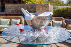 Champagne in a bucket of ice, surrounded by glasses on the sunny Stock Photo