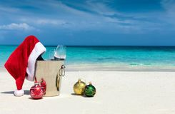 Champagne bucket with Santa hat and Christmas balls. On a tropical beach Royalty Free Stock Photo