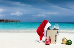 Champagne bucket with Santa hat on tropical location. Christmas holiday concept: champagne bucket with Santa hat on tropical location Stock Photo