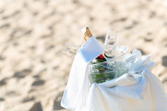 Champagne bucket set. Chilled champagne and wine glasses in bucket setup on the beach. Closeup Stock Photography