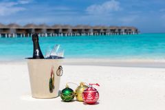 Champagne bucket on a tropical beach with christmas balls. For the holiday season Royalty Free Stock Image