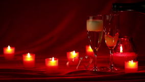 Champagne and candles. Pouring champagne in glasses at Valentines day celebration, still life with candles, roses and hearts on red silk stock footage