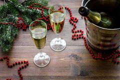 Champagne for celebrate new year. Glasses, bottle in bucket, spruce branch, decoration on wooden background Royalty Free Stock Photography