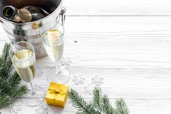 Champagne for celebrate new year. Glasses, bottle in bucket, spruce branch on white wooden background copyspace Royalty Free Stock Images